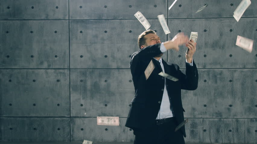 Man in formal suit dancing and throwing money. Slow motion