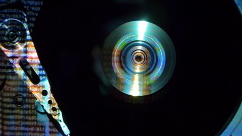 The hdd starts working, the head moves over the disk, the movie is beginning and frames combined with the symbols of the program encoding are reflected on the surface of the disk. Top view. Macro. Clo