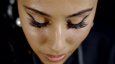 a close shot at the woman's face, the lady raises her eyes with long false eyelashes