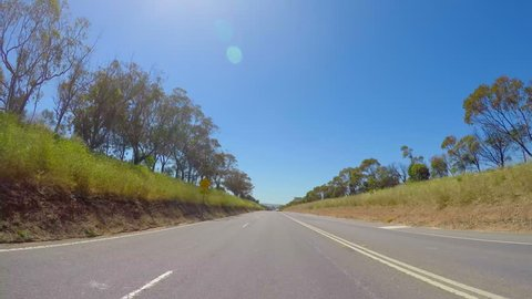 Vehicle POV, driving along country road past rows of grape vines, in McLaren Vale, South Australia.