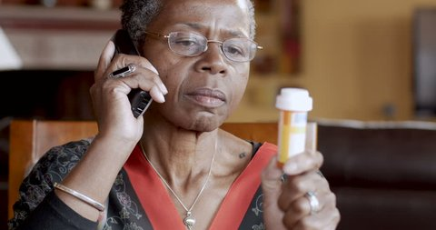 Happy black senior woman refilling her prescription to a pharmacy or talking to her doctor about her health care on a cordless phone