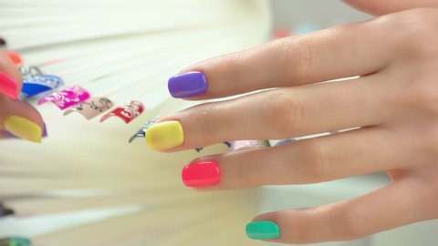 Beautiful summer manicure and nail art samples. Nail art design palette and well-groomed young woman hand close up.