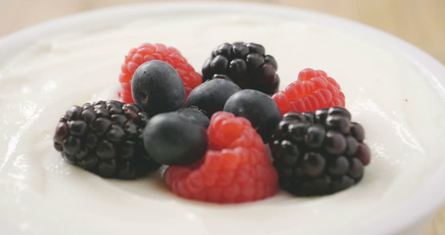 Composition of a typical genuine breakfast made with yogurt, blueberries, raspberries, blackberries, muesli. Concept of: fitness, diet, wellness and breakfasts.