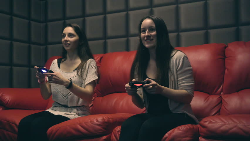 Two young girls playing video games with game controller on red sofa | Shutterstock HD Video #34011673