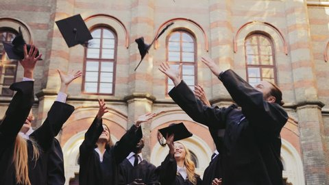 Group of multi ethnical graduates in traditional clothes tossing their caps up in the air happily in front of the University. Outdoors