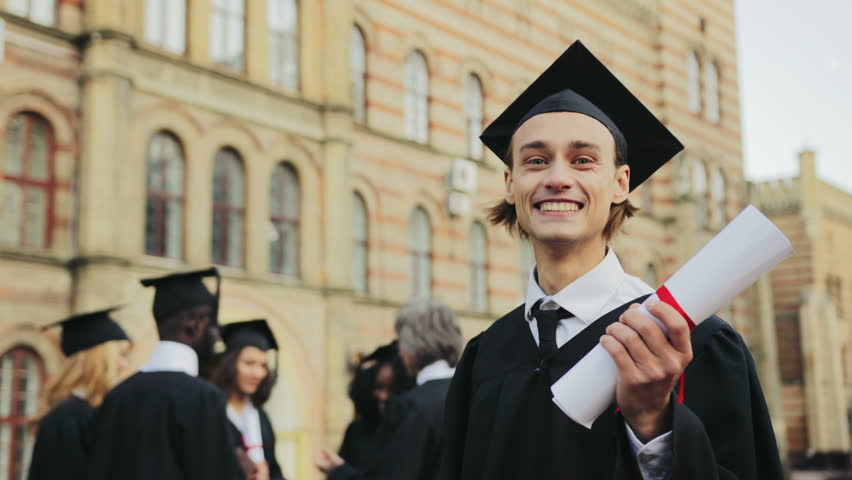 Portrait of the Caucasian happy young graduated man posing to the camera and showing his diploma in front of the University. Graduates with professor on the background. Outdoors