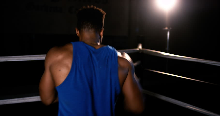Isolated on black, an African-American boxer shadowboxes/practices hits in an empty boxing ring