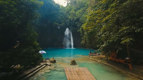 Beautiful waterfall in green forest in jungle. Tropical rain forest with waterfall.Waterfall with natural swimming pool in a mountain river canyon. Kawasan Falls. Philippines, Cebu. 4K video. Travel
