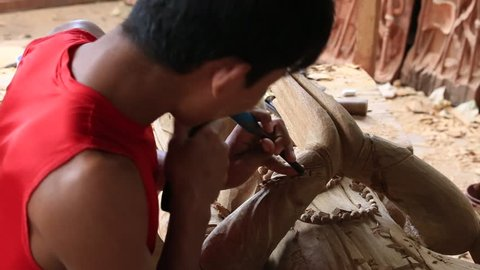 BAGAN. MYANMAR - JANUARY 22, 2016: Burmese man are making wooden souvenirs for tourists in Bagan, Myanmar. Wood Carving is a traditional handicraft in Myanmar