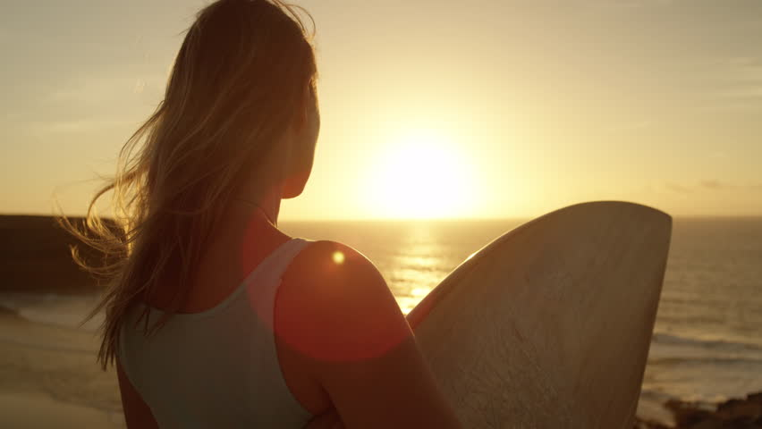 SLOW MOTION CLOSE UP: Surfer girl standing on rocky ocean cliff and watching breaking waves at golden sunset. Woman holding a surfboard, looking the waves at sunrise in Fuerteventura, Canary Islands