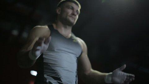 Muscular man prepares to lift heavy barbells