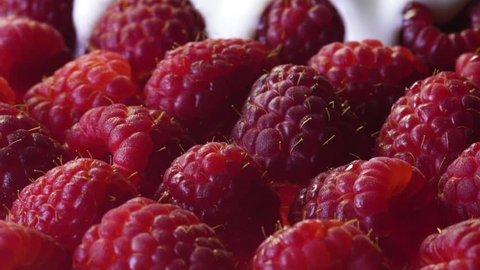 white yogurt poured covering raspberries