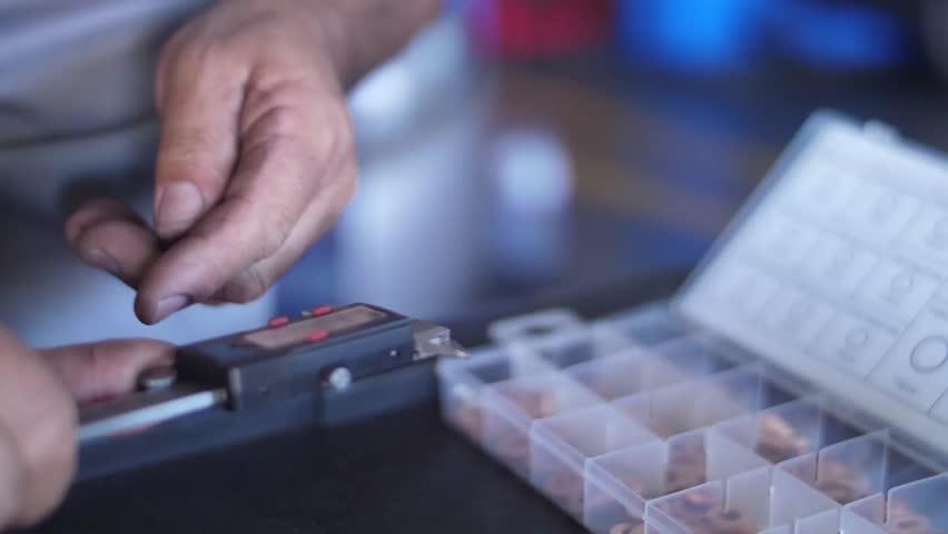 mechanic using a caliper digital thickness gauge micrometer ruler slow motion