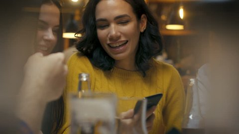 Beautiful Hispanic Woman Uses Smartphone While Talking and Having Fun with Her Friends in the Bar. They Laugh, Joke, Drink in Stylish Hipster Bar Establishment.