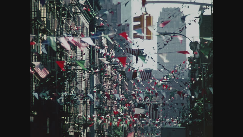NEW YORK, 1971, Flags fluttering overhead above a street in Little Italy
