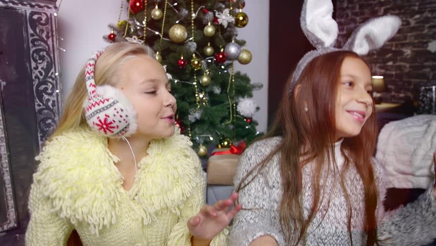 Two Girls in headphones listening music. Chirstmas