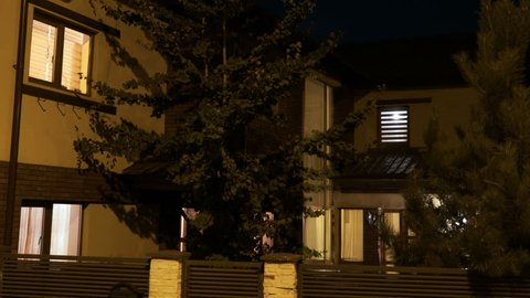 Establishing shot of smart residential house with lights turning on and off on first and second floor