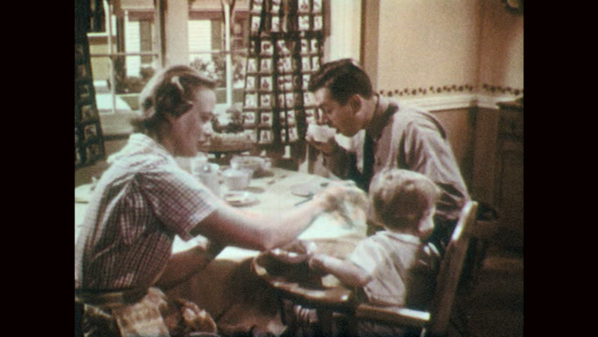 1950s: UNITED STATES: lady wipes baby's face. Family eat breakfast at kitchen table. Man speaks to baby.