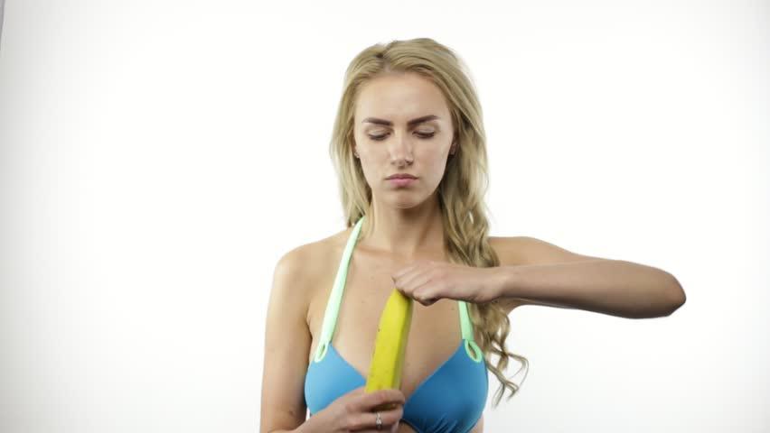 Young woman peeling and eating banana