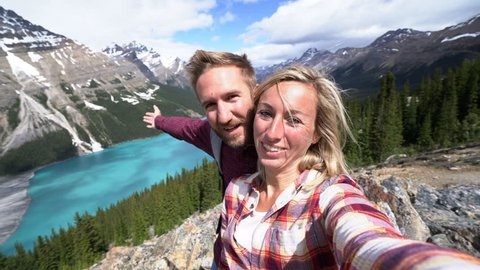 Selfie of young couple hiking in the Canadian Rockies, Banff national park. Shot above Peyto lake in Springtime. People travel sharing concept