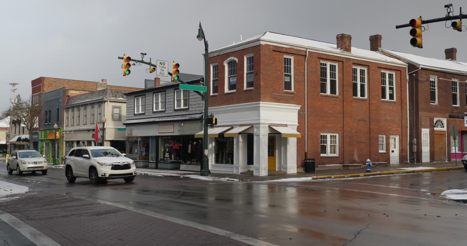 A daytime winter establishing shot of businesses on a typical Main Street in America decorated for Christmas. Building names obscured for general use. Snow plow truck passes by. Pittsburgh suburb.