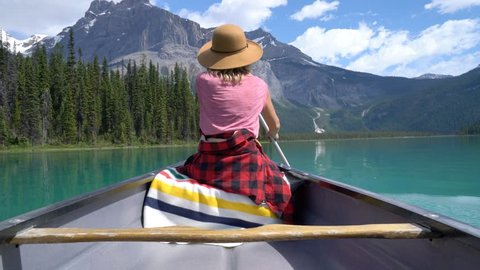 Young woman canoeing on stunning pristine emerald lake. Woman paddling canoe on turquoise lake in the middle of the Canadian rockies. Stunning mountian lake scenery
