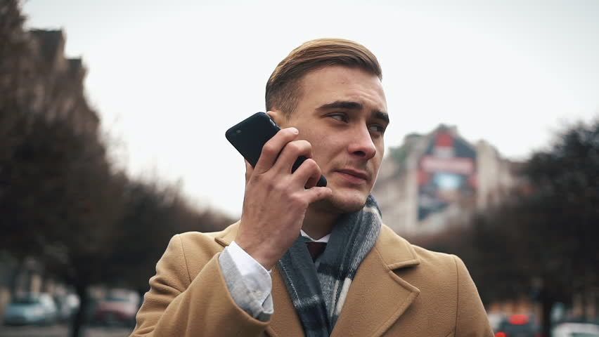 A young businessman in a cloak walking down the street in a cloudy weather and talking on the phone | Shutterstock HD Video #34266883