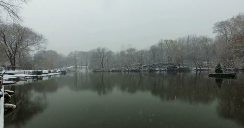 Beautiful scenery of Central Park in New York covered in snow on a cold december day while snowing. Pan right overlooking a small lake with trees.