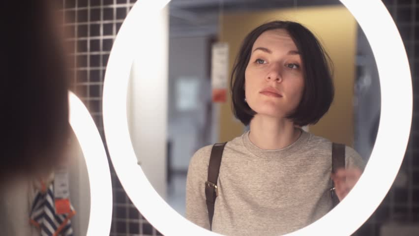 Young woman looking in mirror in department store. Customer chooses bedroom goods. Slow motion | Shutterstock HD Video #34276483
