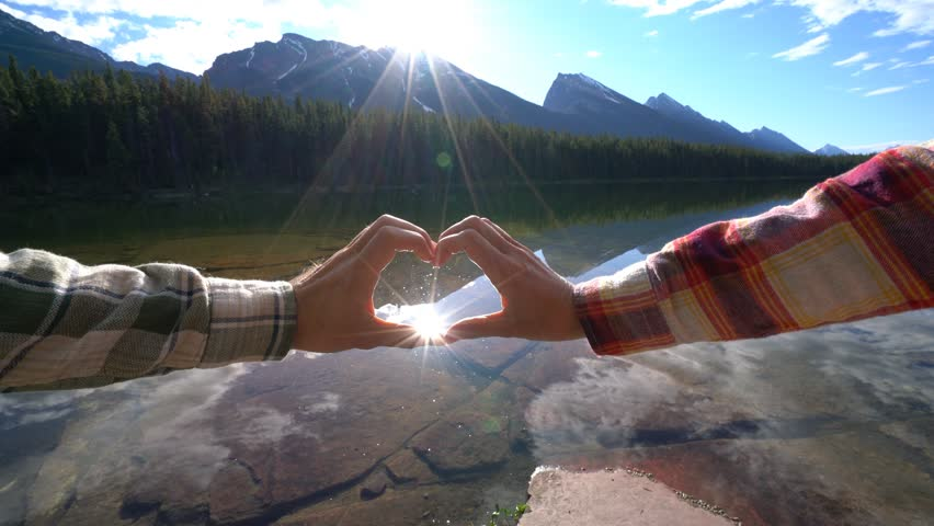 Close up on hands making heart shape frame on mountain lake landscape in Jasper national park, Alberta, Canada. People travel environment nature concept