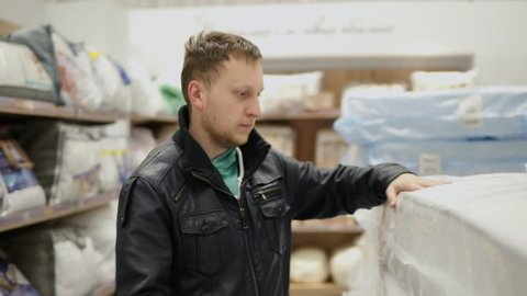 Young man is choosing a mattress in a big furniture shop or supermarket. He is checking its elasticity, memory foam by pressing on it