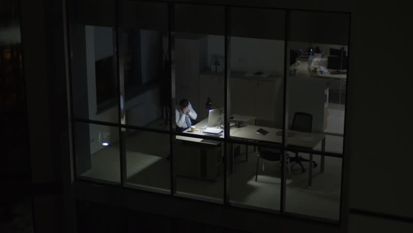 View from outside of modern glass office of tired overworked businessman drinking coffee and rubbing his face in front of computer at night
