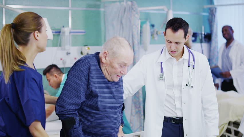 An attractive and caring young doctor and nurse help an elderly male patient to walk. Other doctors and nurses can be seen attending to other jobs in the background. In slow motion. #3432413