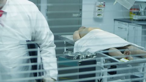 The lifeless naked corpse of a young mixed race male is laid out on the autopsy table, ready for the medical examiner to begin his work. He checks the toe tag and starts to make notes.