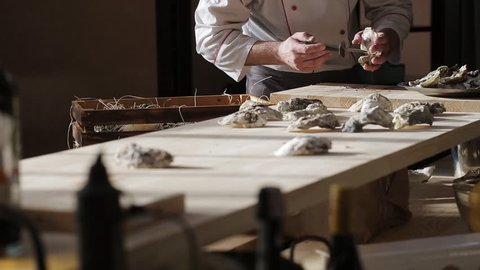 Chef in a luxury fish restaurant opens oysters on the table and puts them on a plate with ice
