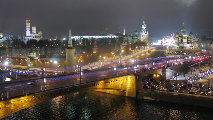 Night traffic on bridge across the river . Timelapse