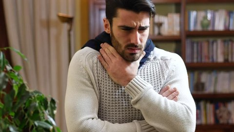 Young man with scarf, holding his neck because of cold and throat-ache, coughing, at home in his living room
