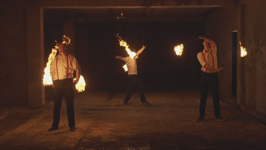 Group of male artists performing fire show at dark abandoned building in slow motion. Fireshow in ruins at night.