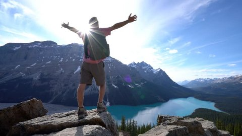 Hiker reaches mountain top above lake, arms outstretched. Young man hiker reaches the top of the mountain and outstretches his arm. Achievement in nature