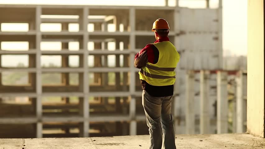 Builder looks at new construction site. Worker in hard hat stands on project site and looks at new building structure on the sunset | Shutterstock HD Video #34401613