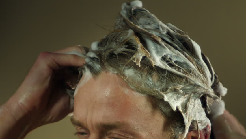 Close up of male blonde hair being washed with shampoo foam