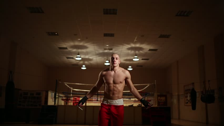 A pumped-up man in boxing shoes and shorts in the gym against the backdrop of a boxing ring. The camera moves on a Steadicam | Shutterstock HD Video #34417393