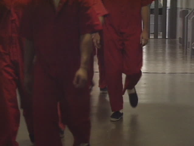 A group of prisoners in orange jump suits.