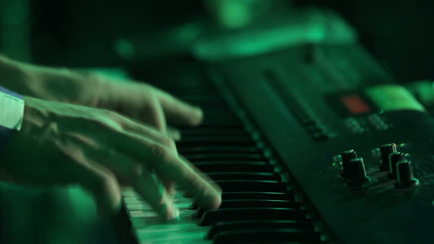 Hands playing music on the piano keyboard on rock concert