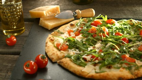 Traditional Italian pizza with arugula, cheese, yoghurt and cherry tomatoes close up, Caprese Homemade delicious vegetarian pizza on wooden table. 4K UHD video