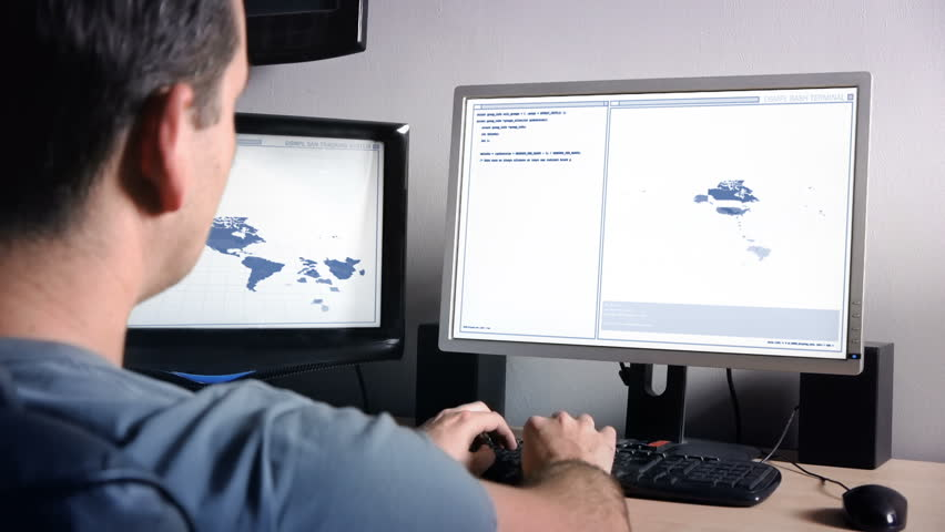 Programmer working with multiple monitors and tracking data on animated world map. Dolly Shot.