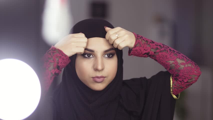 Close-up portrait of a muslim woman in national clothes adjusting her hijab while looking in the mirror. Slow motion