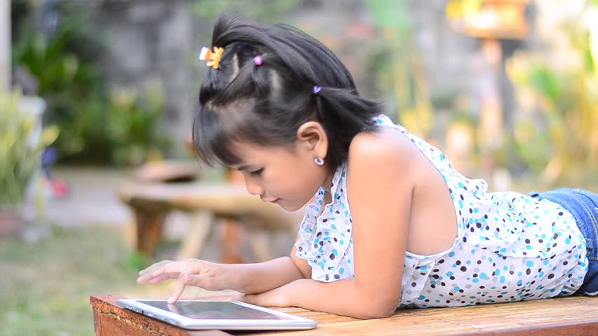 Asian little girl playing a game on computer tablet