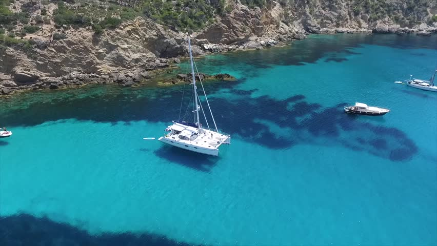 Summer Chilling Fun vibes! Beautiful drone video of a sail boat anchored in a turquoise cove. This Catamaran super yacht is the perfect place to relax! 1080p 60fps.
