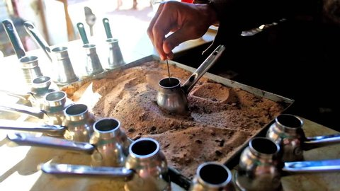 Roadside cafe in bedouin village offers hot, tasty, strong coffee, boiling in cezve on the sand, Sinai, Egypt.